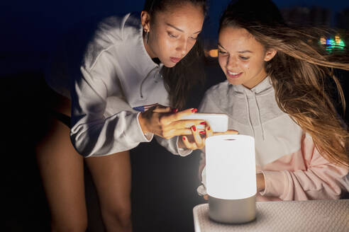 girls on the beach looking a smartphone and smiling lit with led light/SPAIN/ALICANTE/ALICANTE - DLTSF00158