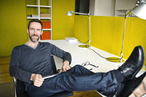 Portrait of smiling businessman in office with feet on desk - MIK00012