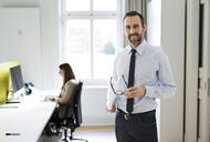 Portrait of smiling businessman in office with employee in background - MIKF00021