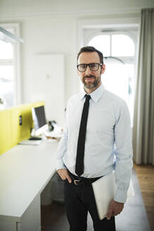 Portrait of confident businessman in office with employee in background - MIKF00024