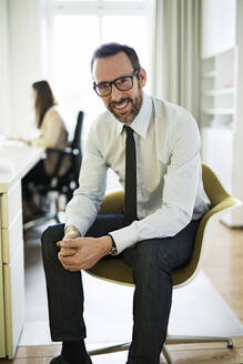 Portrait of smiling businessman in office with employee in background - MIKF00027