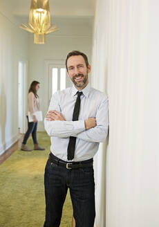 Portrait of smiling businessman leaning against the wall on office floor - MIK00042