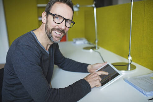 Portrait of smiling businessman using tablet at desk in office - MIK00051