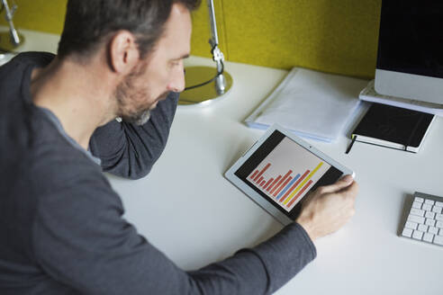 Businessman analyzing bar chart on tablet in office - MIK00054