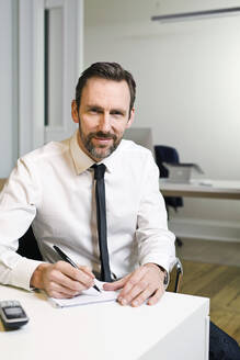 Portrait of confident businessman sitting at desk in office taking notes - MIK00057