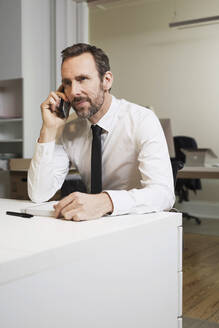 Businessman talking on the phone at desk in office - MIK00060