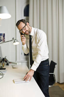Smiling businessman talking on the phone in office - MIK00066