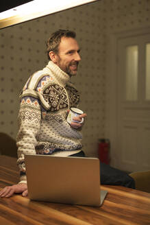 Smiling casual businessman with laptop on table at home - MIK00072