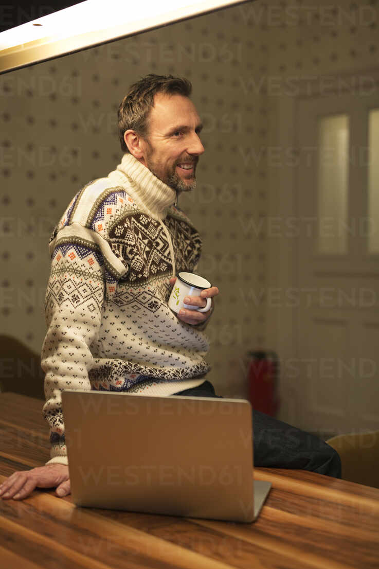 Smiling casual businessman with laptop on table at home - MIK00072 - Fritz Miller/Westend61