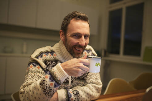 Portrait of happy casual businessman with mug sitting at table at home - MIKF00075
