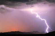 A bright lightning strike illuminating the Buckeye Foothills in Arlington during the 2012 Monsoon season, Arizona, United States of America, North America - RHPLF11829