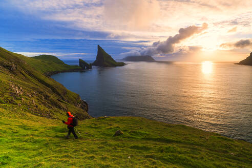 Trekker on the hiking trail to Drangarnir rock, Vagar island, Faroe Islands, Denmark, Europe - RHPLF12096