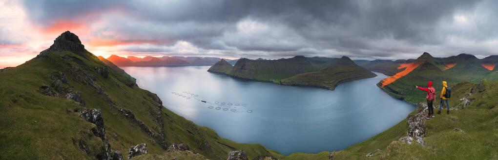 Panoramic of hikers on cliffs looking to the fjords, Funningur, Eysturoy island, Faroe Islands, Denmark, Europe - RHPLF12102
