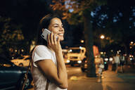 Young woman using smartphone in the city at night - OYF00065