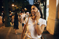 Young woman using smartphone in the city at night - OYF00068