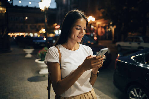 Young woman using smartphone in the city at night - OYF00071