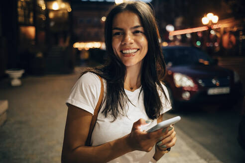 Young woman using smartphone in the city at night - OYF00074