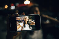 Young woman using smartphone in the city at night, taking a selfie - OYF00083