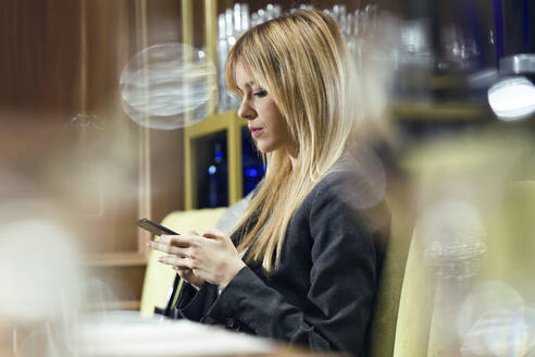 Businesswoman using cell phone in a restaurant - JSRF00605