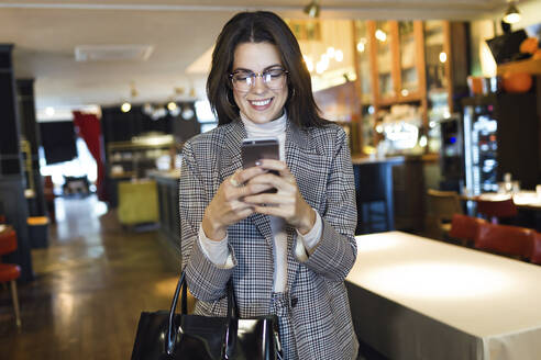 Smiling businesswoman using cell phone in a restaurant - JSRF00611