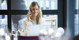 Smiling businesswoman using cell phone and laptop in a restaurant - JSRF00617