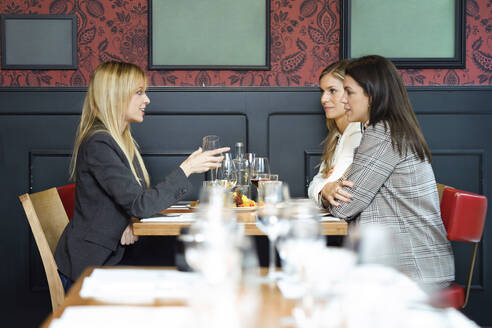 Three businesswomen talking while eating together in a restaurant - JSRF00623