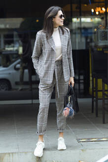 Smiling stylish woman standing outside a restaurant looking around - JSRF00629
