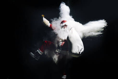Santa Claus with exploding snow bomb against black background - OCMF00748