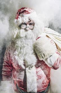 Close-up Santa Claus posing among icy smoke in snow - OCMF00751