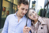 Portrait of happy couple with umbrella in Ginza, Tokyo, Japan - MCVF00024