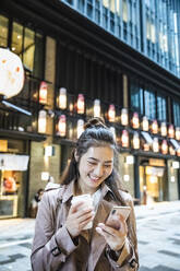 Happy young woman holding takeaway drink and using smartphone in Ginza, Tokyo, Japan - MCVF00027