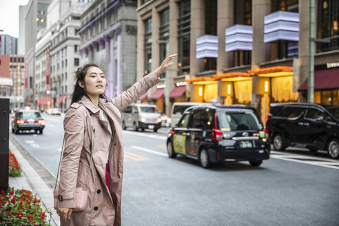 Young woman hailing a taxi at a street in Ginza, Tokyo, Japan - MCVF00033