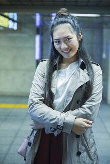 Portrait of smiling young woman at Ginza underground station, Tokyo, Japan - MCVF00036