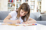 Portrait of girl drawing with coloured pencil at home - LVF08268