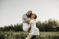 Young laughing couple, man carrying woman - LHPF00860