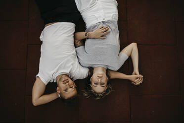 Young couple lying on the ground, from above - LHPF00863