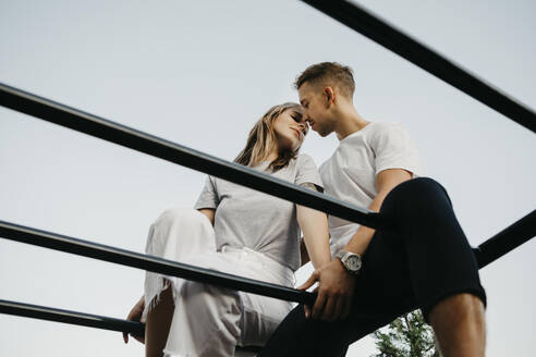 Young couple kissing each other on a climbing frame - LHPF00875