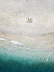 Aerial view of young women lying at the beach, Gili Air island, Bali, Indonesia - KNTF03447