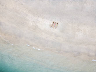 Aerial view of young women lying at the beach, Gili Air island, Bali, Indonesia - KNTF03453