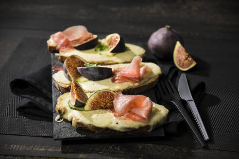 High angle view of baked cheese bread with fig and ham served on table - MAEF12944