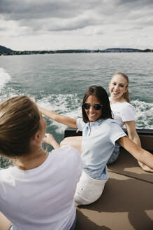 Happy female friends on a boat trip on a lake - LHPF00893