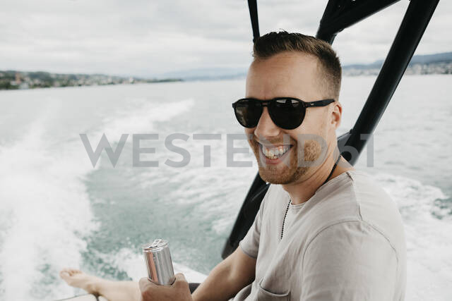 Happy man wearing sunglasses on a boat trip on a lake - LHPF00905 - letizia haessig photography/Westend61