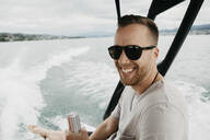 Happy man wearing sunglasses on a boat trip on a lake - LHPF00905