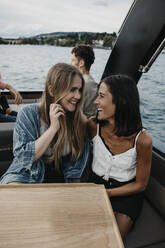 Happy friends on a boat trip on a lake - LHPF00923