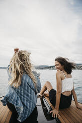 Happy female friends on a boat trip on a lake - LHPF00926