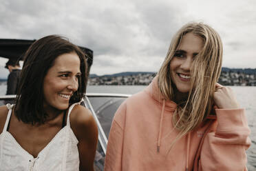 Happy female friends on a boat trip on a lake - LHPF00929