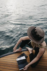 Woman with a book on a boat - LHPF00935