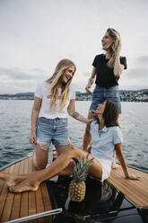 Happy female friends having fun on a boat trip on a lake - LHPF00947