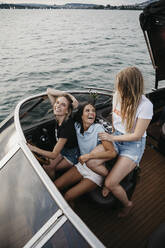 Happy female friends having fun on a boat trip on a lake - LHPF00950