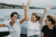 Happy female friends having fun on a boat trip on a lake - LHPF00953